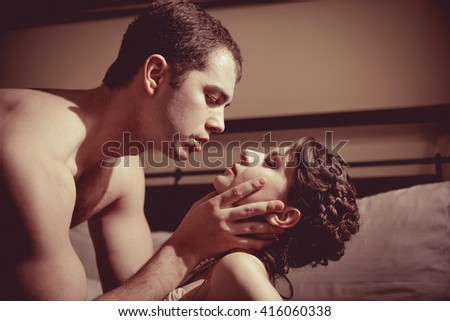 Beautiful couple is kissing in the bedroom. Retro styled toning. - stock photo