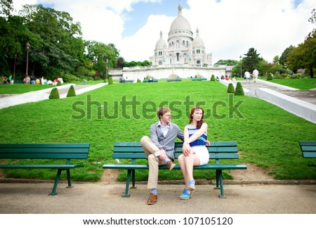 Beautiful couple is sitting on the bench near the Sacre-Coeur basilica in Paris - stock photo