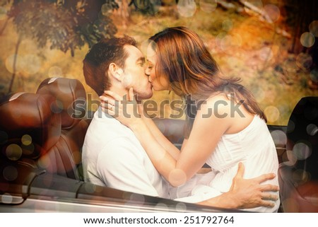 Beautiful couple kissing in back seat of a convertible - stock photo