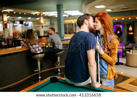 Beautiful couple kissing in billiards bar on their date - stock photo