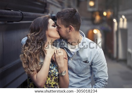 beautiful couple kissing on one of London's streets - stock photo