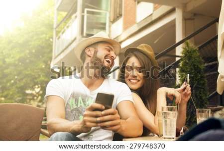 Beautiful couple laughing at the cafe while using smart phone  - stock photo