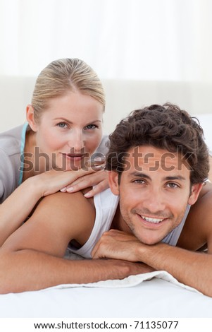 Beautiful couple lying down on their bed at home