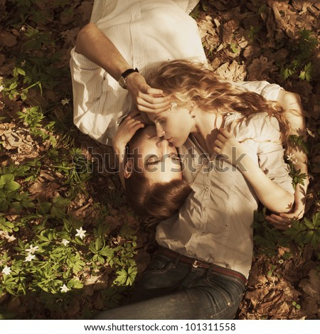 beautiful couple lying in a meadow in spring - stock photo