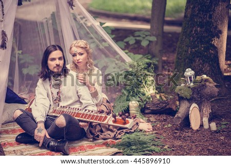 Beautiful couple man and a girl sitting in a white tent in the eastern ethnic costumes, the man playing the sitar, love, music, relationships