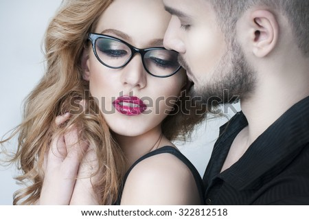 Beautiful couple. Man hugging a blond woman. Woman wearing eyeglasses. Passionate couple in love. Portrait of beautiful woman handsome man. Love. Kiss. Flirt. Lovers. - stock photo