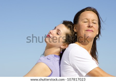 Beautiful couple mother and daughter sitting relaxed with closed eyes back to back in sunshine, with clear blue sky as background and copy space.