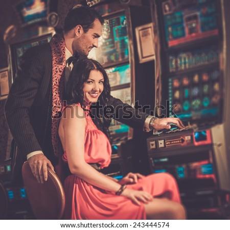Beautiful couple near slot machine in a casino - stock photo