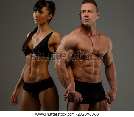 Beautiful couple of bodybuilder and fitness women. Isolated on grey background. - stock photo