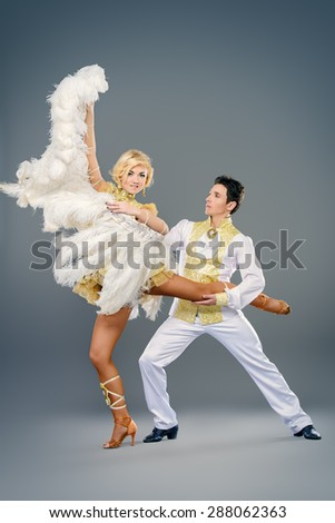 Beautiful couple of dancers dancing at studio in white lush costumes with wings. Show-ballet.