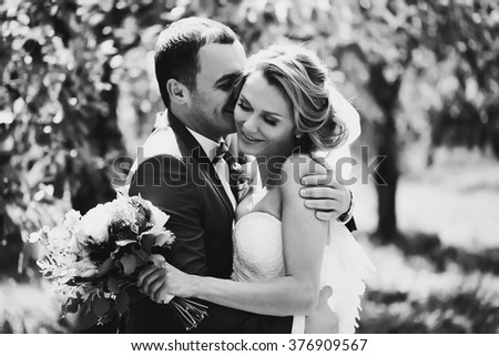 Beautiful couple of happy stylish newlyweds on a walk in the sunny summer park or garden on their wedding day