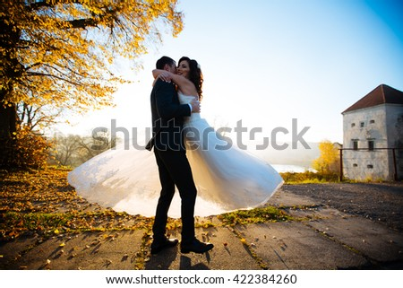 Beautiful couple of happy stylish newlyweds on a walk in the sunny summer park or garden on their wedding day - stock photo
