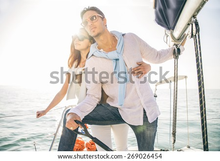 Beautiful couple of lovers sailing on a boat - Young attractive man holding rudder of a yacht and looking far away - Two fashion models posing on a sailing boat at sunset - stock photo