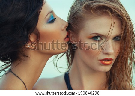 Beautiful couple of models with perfect arty make-up on the beach. Long wet hair and waterproof decorative cosmetics. Close up. American disco (vintage) style. Outdoor fashion shot - stock photo
