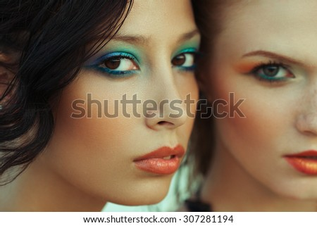 Beautiful couple of models with perfect arty make-up. Wet hair and waterproof decorative cosmetics. Close up. American disco (vintage) style. Outdoor fashion shot