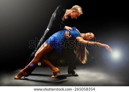Beautiful couple of professional artists dancing on black background - stock photo
