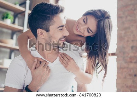 Beautiful couple of young lovers are hugging indoors at home, looking at each other with love and tenderness, wearing white casual clothes