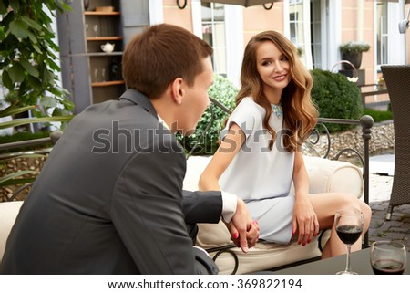 Beautiful couple on a date at restaurant lunch, dinner, flirt talking. Valentine's Day holiday of lovers, husband and wife man and woman happy relationship the proposal  love, happiness, holding hands