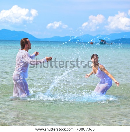 beautiful couple on the beach in wedding dress playing in the water - stock photo