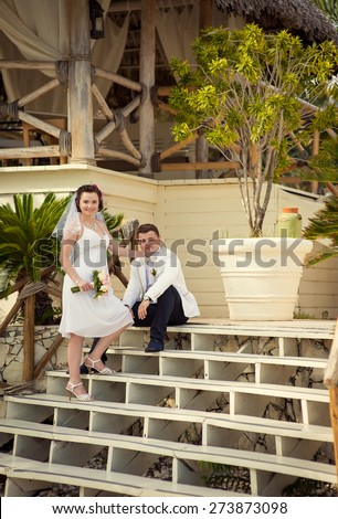 beautiful couple on the beach in wedding dress. young loving couple on tropical sea background - wedding on beach - stock photo