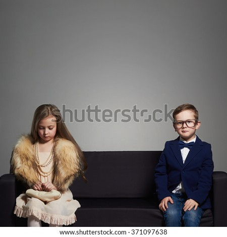 beautiful couple on the couch.beauty little girl in dress and boy in suit and glasses.stylish kids