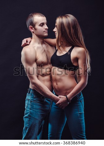 Beautiful couple on the dark background, Both of them with naked torso. Woman in sport bra.  They in love.
