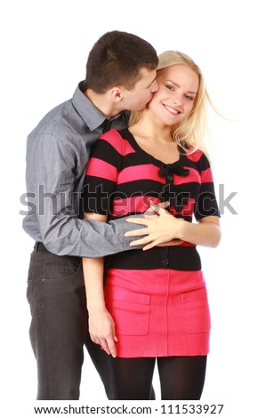 Beautiful couple on white. Careful man kissing his smiling girlfriend on the cheek