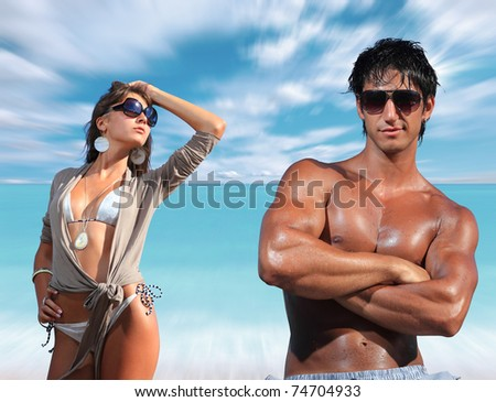 beautiful couple posing at the beach - stock photo