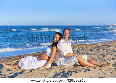 Beautiful couple pregnant woman in the beach sitting on sand happy together back to back - stock photo