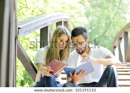 Beautiful couple reading book outdoors - stock photo