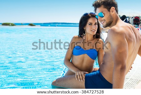 Beautiful Couple Resting By The Pool During The Holidays - stock photo