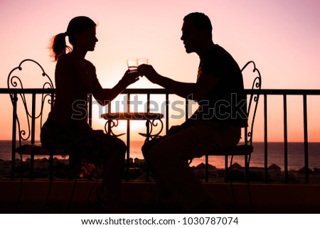 Beautiful couple silhouette on nature near the sea on a rift background