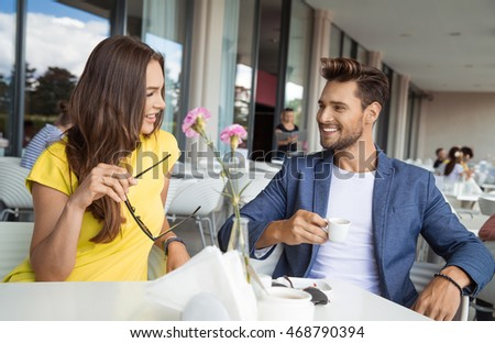 Beautiful couple sitting in restaurant talking and smiling