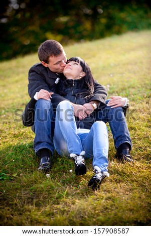 Beautiful couple sitting on grass and kissing