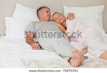 Beautiful couple sleeping on their bed - stock photo