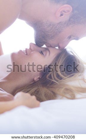 Beautiful couple spending romantic moments in bed - stock photo