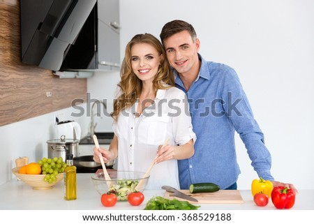 Beautiful couple standing and cooking together on the kitchen at home  - stock photo