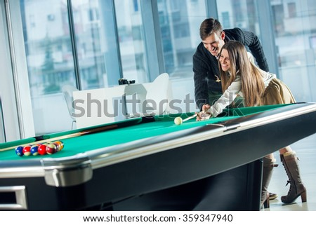 Beautiful couple standing next to the pool table, selective focus - stock photo