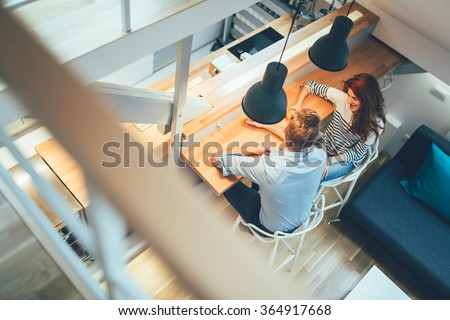 Beautiful couple talking in their pristine home while sitting at kitchen counter - stock photo