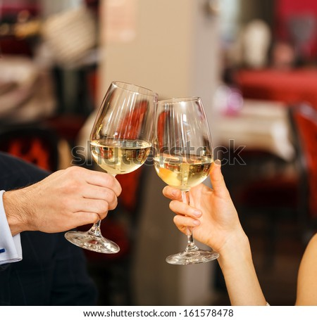Beautiful couple toasting wineglasses in a restaurant