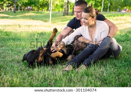 Beautiful couple walking a dog in park. Focus on couple