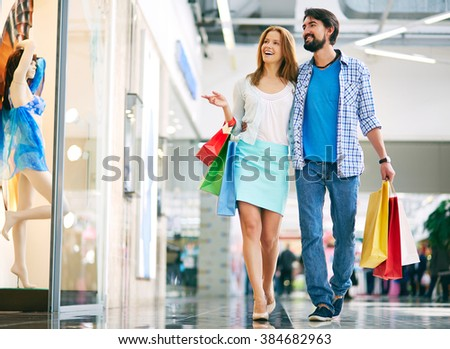 Beautiful couple walking through the mall and carrying shopping bags
