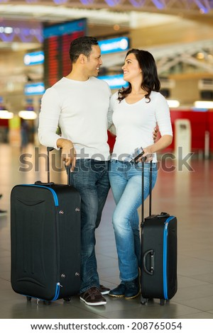 beautiful couple with luggage bags at airport - stock photo