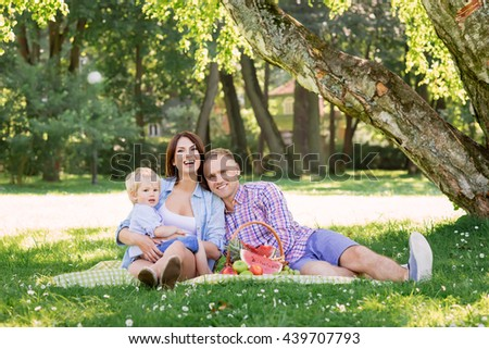 Beautiful couple with toddler son having a picnic in the park.