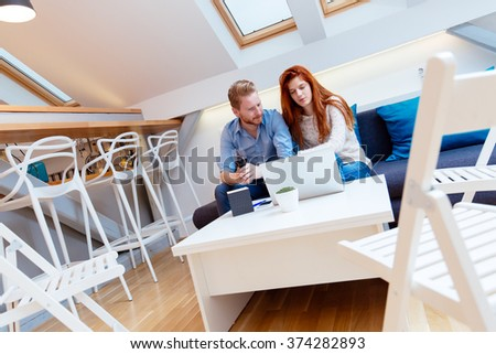 Beautiful couple working on laptop in beautiful living room while sitting on sofa