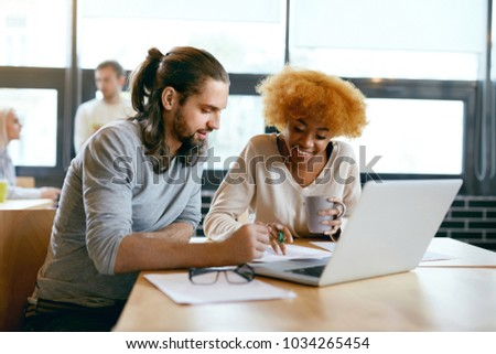Beautiful Couple Working On Notebook In Cafe. Smiling Young Man And Happy Woman Working Together, Looking At Laptop And Sharing Ideas In Coffee Shop. High Quality Image.
