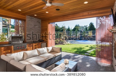 Beautiful covered patio with barbecue, fan, sink, and couch, behind new luxury home. View of landscaped lawn and private basketball court