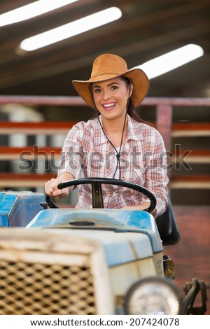 beautiful cowgirl driving tractor inside stables