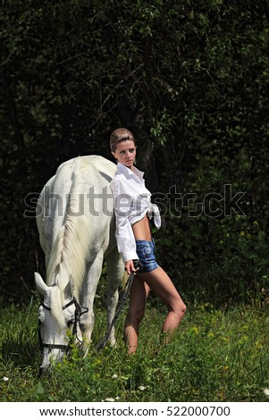 Beautiful cowgirl feeding horse on the farm