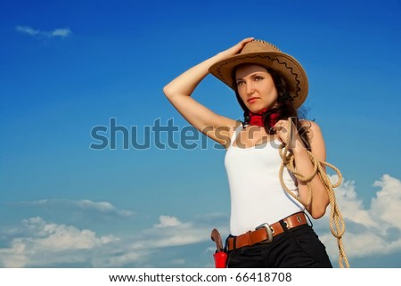 Beautiful cowgirl in a cowboy hat - stock photo